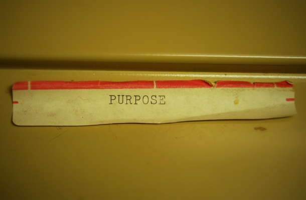 "A worn label that reads ""PURPOSE"" at the bottom of a file."