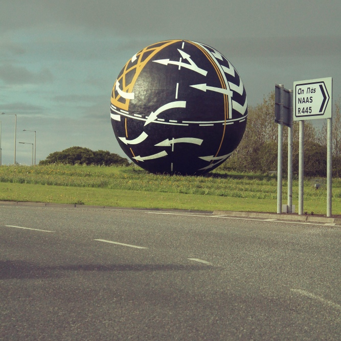 A building-sized black ball with white arrows and yellow paint.