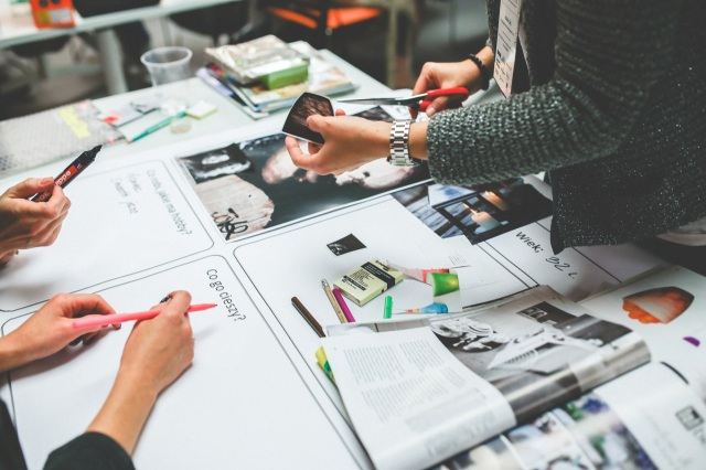 women designing with paper at office desk