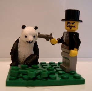 Photo of a lego man holding a lego gun to a panda