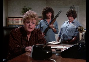 Jessica Fletcher at a desk with two women prisoners behind her