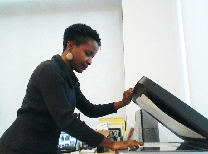 Photograph of Gina Murrell working at a flatbed scanner.