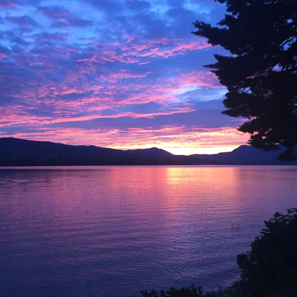 A sunset over a lake with mountains in the background
